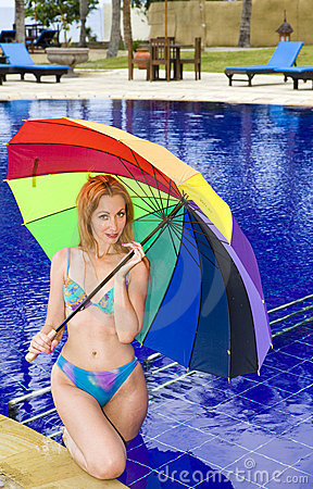 The young attractive woman at pool under a colour