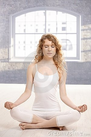 Young attractive woman practicing yoga meditating