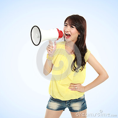 Young attractive woman shouting using megaphone