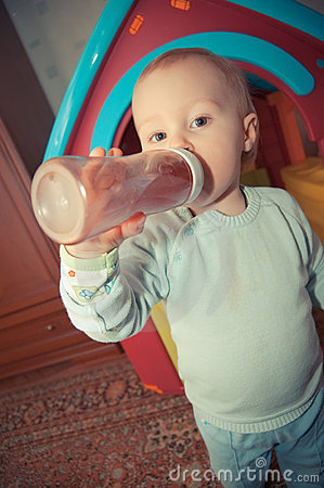 Young baby boy with bottle of juice
