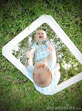 Young Baby Looking At Self In Mirror While Smiling Stock