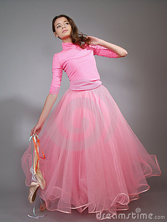 Young ballerina in a pink dress shows modern dance
