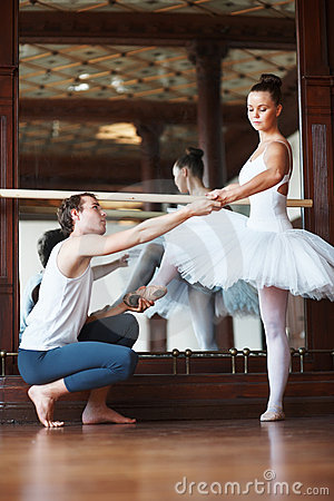 Young ballet trainer training a female dancer
