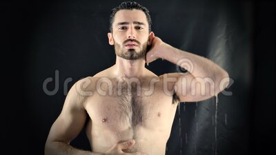 Young Bare Muscular Young Man Receiving Water Splashes in Studio stock footage
