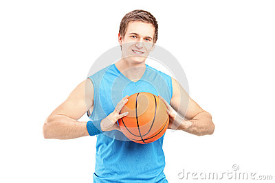 A young basketball player holding a basketball and looking at ca