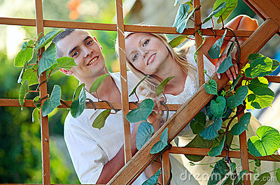 Young bautiful couple at the wooden lattice