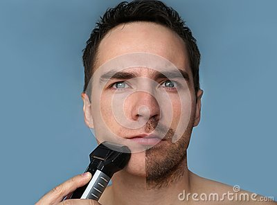 Young bearded man during grooming of beard using trimmer. Half face with a beard half shaved Stock Photo
