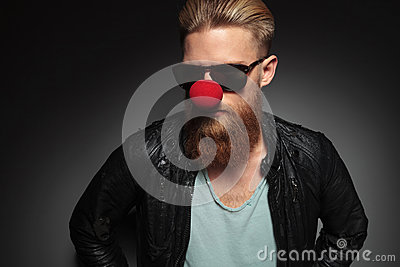 Young bearded man with red clown nose