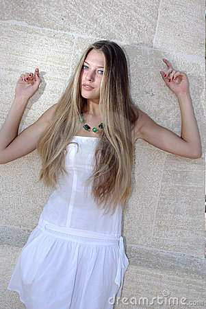 Young beaty in white over wall