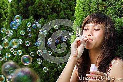 Young beautiful asian having fun with bubble