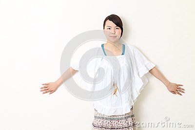 Young beautiful asian woman leaning against wall
