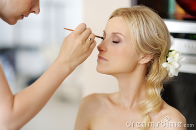 Young beautiful bride applying wedding make-up Stock Photo