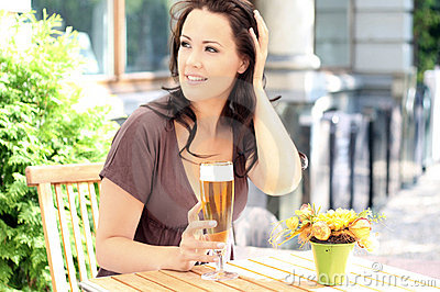 Young beautiful brunette with a beer glass
