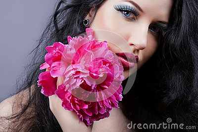 Young beautiful brunette  girl with pink flower