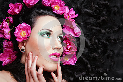 Young beautiful brunette  girl with pink flowers i