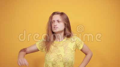 Brunette girl in yellow t-shirt over isolated orange background shows emotions. Young beautiful brunette girl in yellow t-shirt over isolated orange background stock video footage