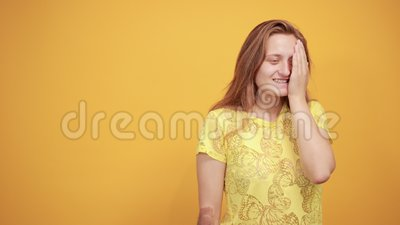 Brunette girl in yellow t-shirt over isolated orange background shows emotions. Young beautiful brunette girl in yellow t-shirt over isolated orange background stock video