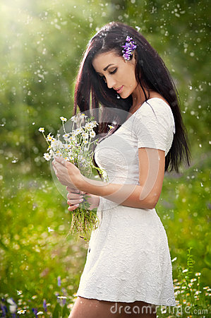 Free Young Beautiful Brunette Woman Holding A Wild Flowers Bouquet In A Sunny Day. Portrait Of Attractive Long Hair Female In White Royalty Free Stock Photography - 45917357