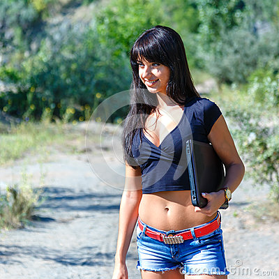 Free Young Beautiful Brunette Woman Holding Laptop Walking Outdoors. Stock Photography - 91727402