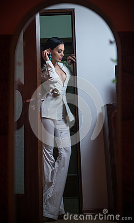 Free Young Beautiful Brunette Woman In Elegant White Suit With Trousers Standing In Door Frame. Seductive Dark Hair Girl Posing Indoors Stock Photography - 68400182