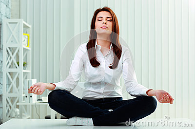 Young beautiful businesswoman meditates on the table