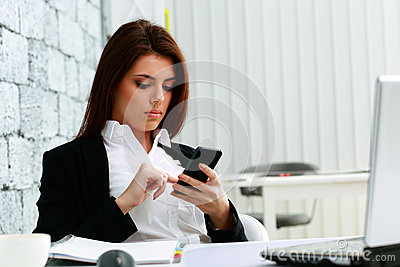 Young beautiful businesswoman typing on her smartphone