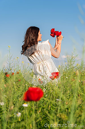 Young beautiful calm girl dreaming on a poppy field, summer outdoor.