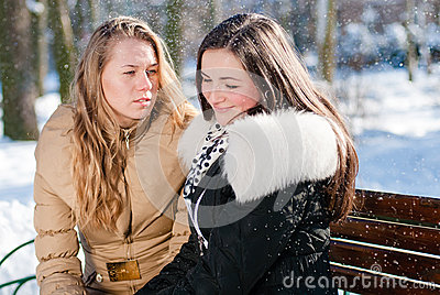2 young beautiful charming women sitting on a bench in winter park outdoors