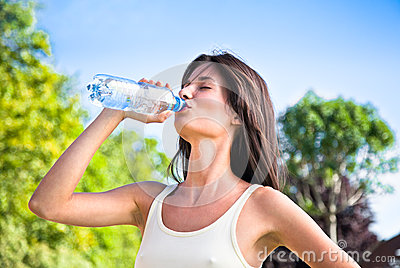 Young  beautiful dark-haired woman drinking water
