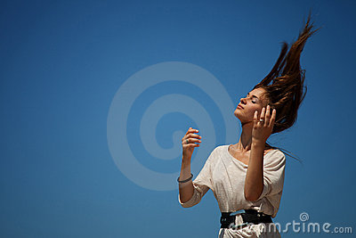 Young beautiful girl against a blue sky