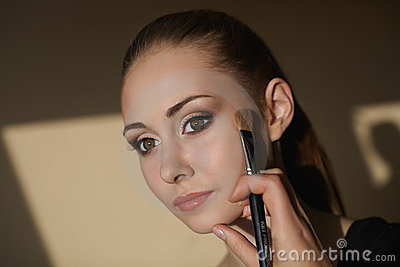 Young beautiful girl applying makeup by makeup