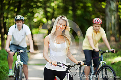 Young beautiful girl on a bicycle with two men in the background