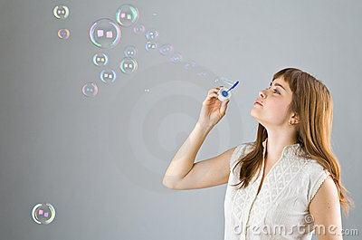 Young beautiful girl blow out soap bubbles