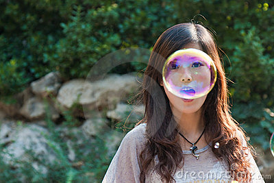 Young beautiful girl blowing bubbles in the nature