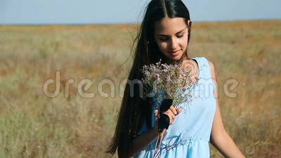 Young Beautiful Girl In A Blue Dress Enjoys Flowers Steppe. A Young Woman In A Meadow. Steppe. Blossoming Sunny Meadow Stock Video - Video of enjoy, outside: 77305079