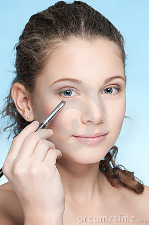 Young beautiful girl doing make-up by brush