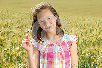 Young beautiful girl in a field of wheat