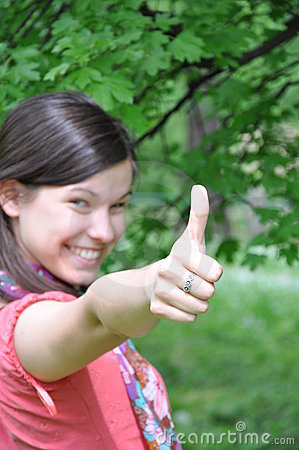 Young beautiful girl holding a thumb up