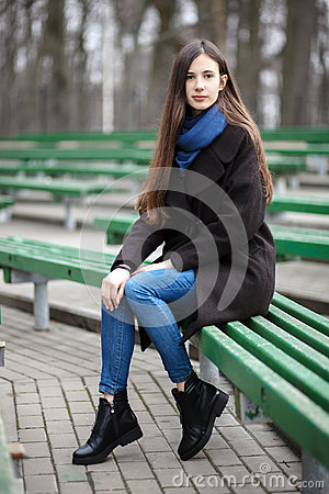 Free Young Beautiful Girl In A Black Coat Blue Scarf Glasses Sitting On Bench In City Park. An Elegant Brunette Girl With Gorgeous Extr Stock Photo - 89346550