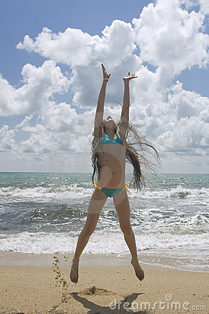 Young beautiful girl jumping at the beach