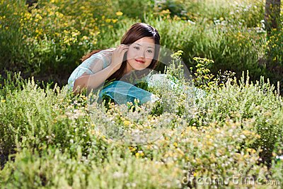 Young beautiful girl laying on the flowers field