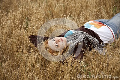 Young beautiful girl lying at yellow autumn field.