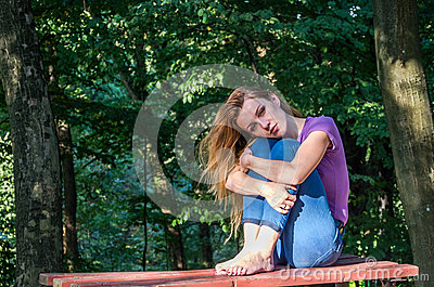 Young beautiful girl model in jeans and a T-shirt with long blond hair and sad smiles pensively posing for a walk in the autumn pa Stock Photo