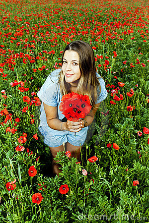 Young beautiful girl in a poppies field