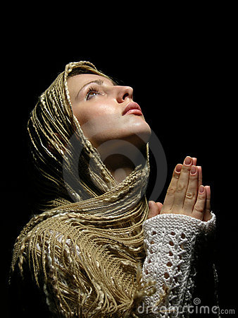 Young and beautiful girl praying with open eyes