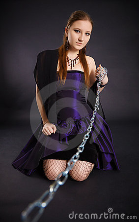 Young beautiful girl pulls out a chain leash