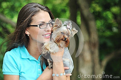 Young beautiful girl with a puppy in a park