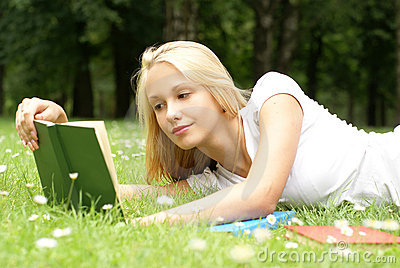 A young and beautiful girl is reading a book
