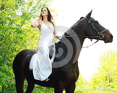 Young beautiful girl riding on horse