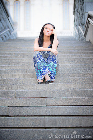 Young beautiful girl sits on steps